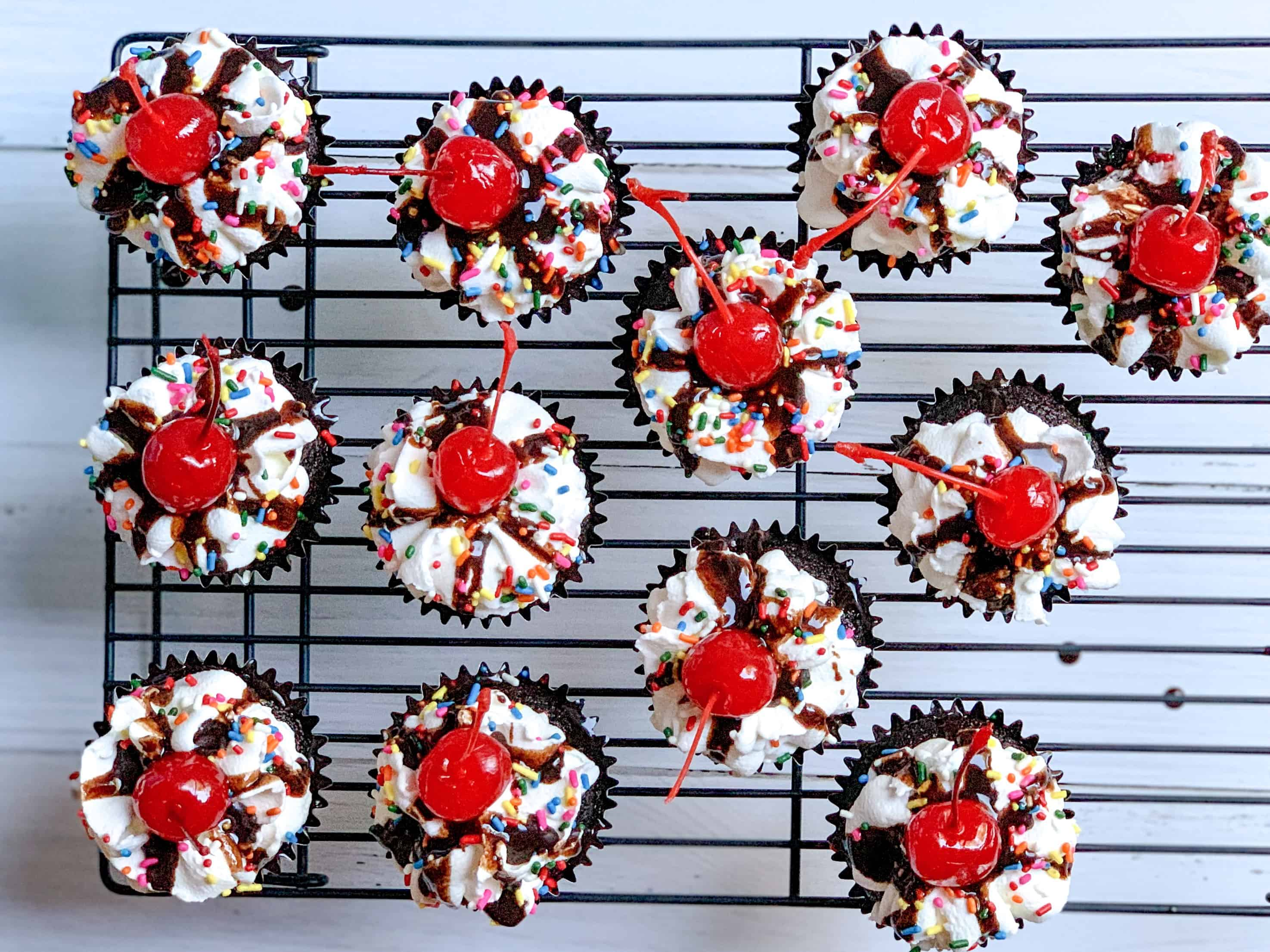 aerial view of 12 cupcakes on black cooling rack.