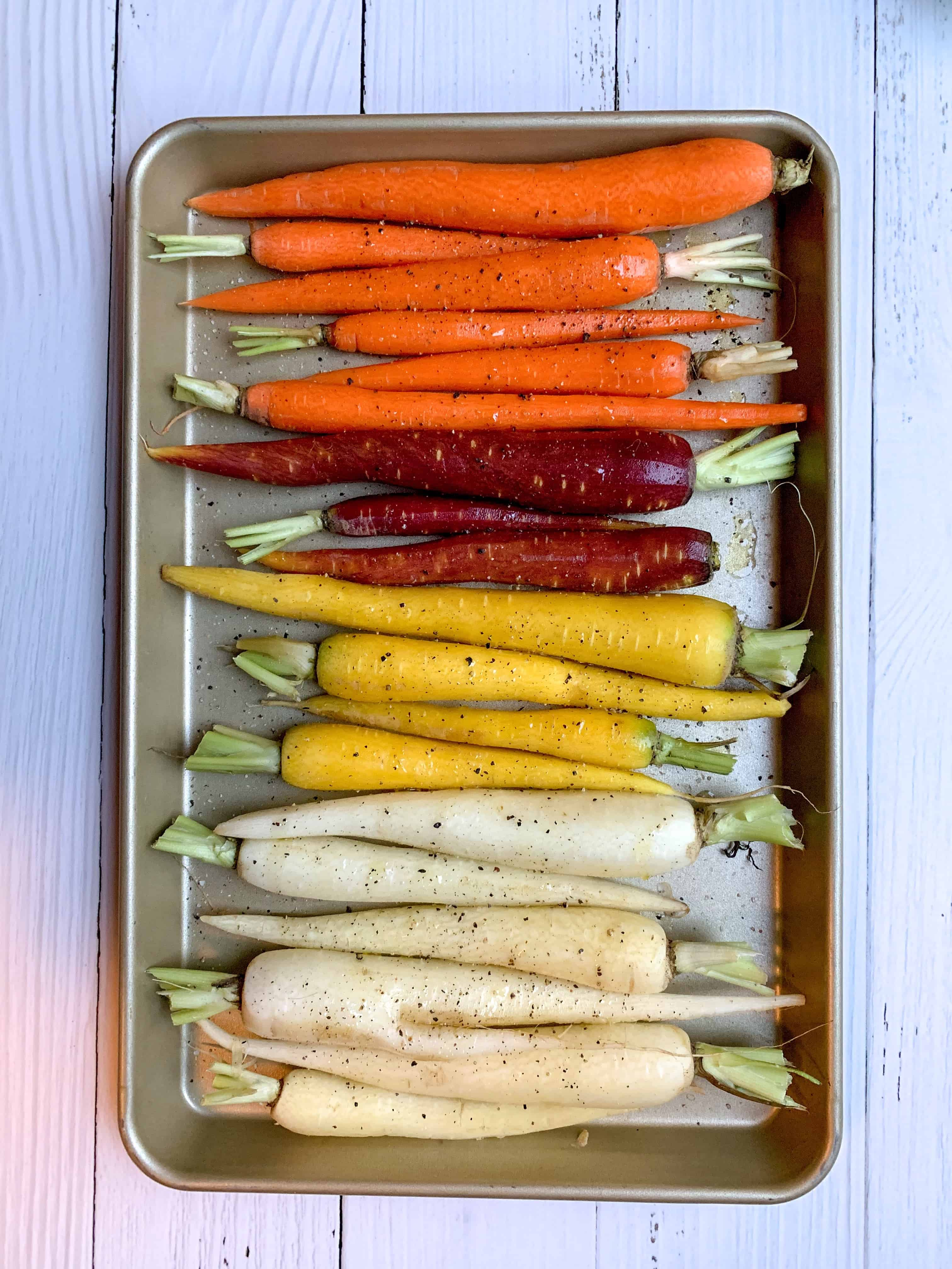 rainbow carrots on a baking sheet with salt, pepper, and olive oil