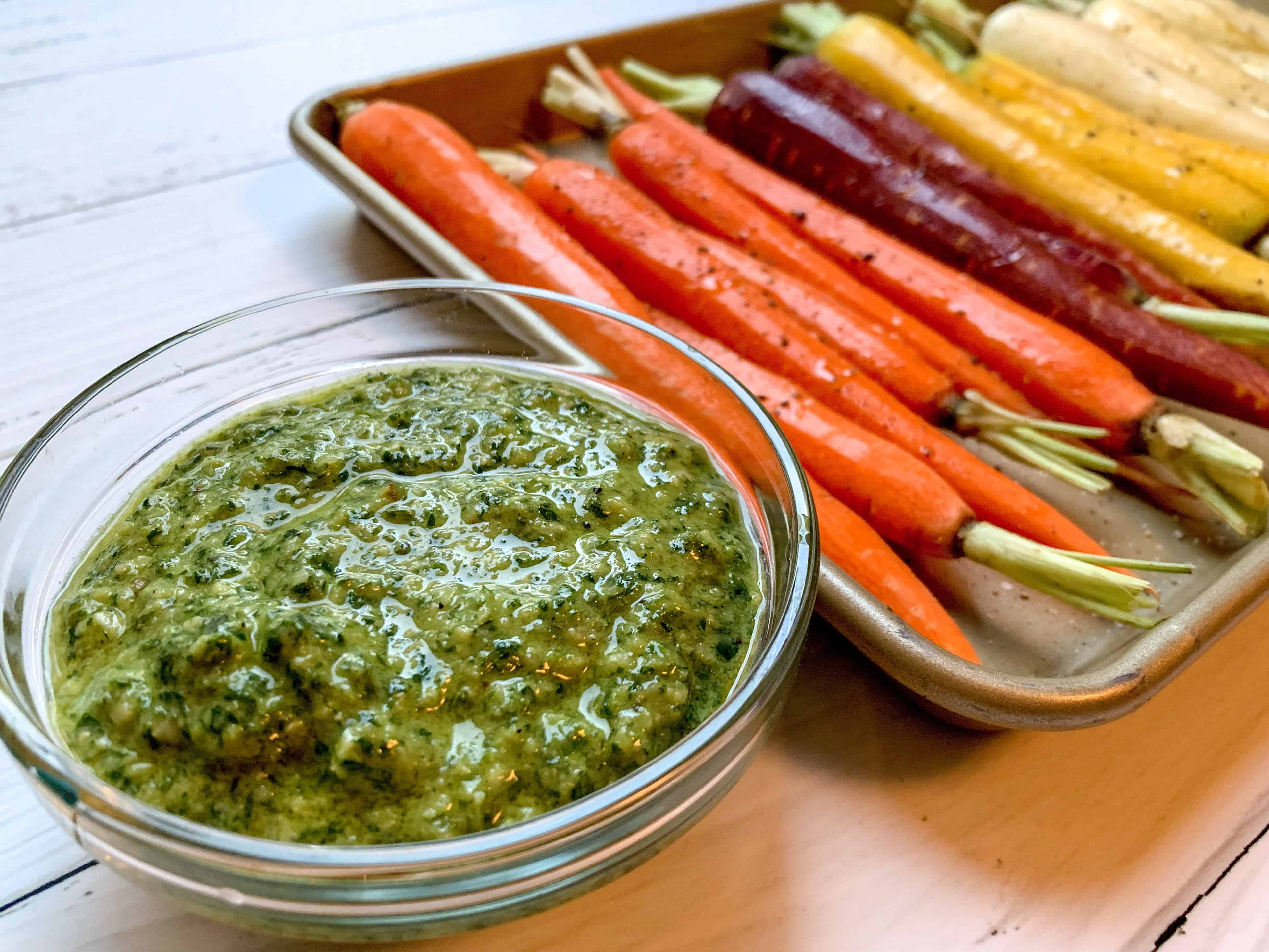 rainbow carrots on baking sheet with bowl of pesto next to sheet.