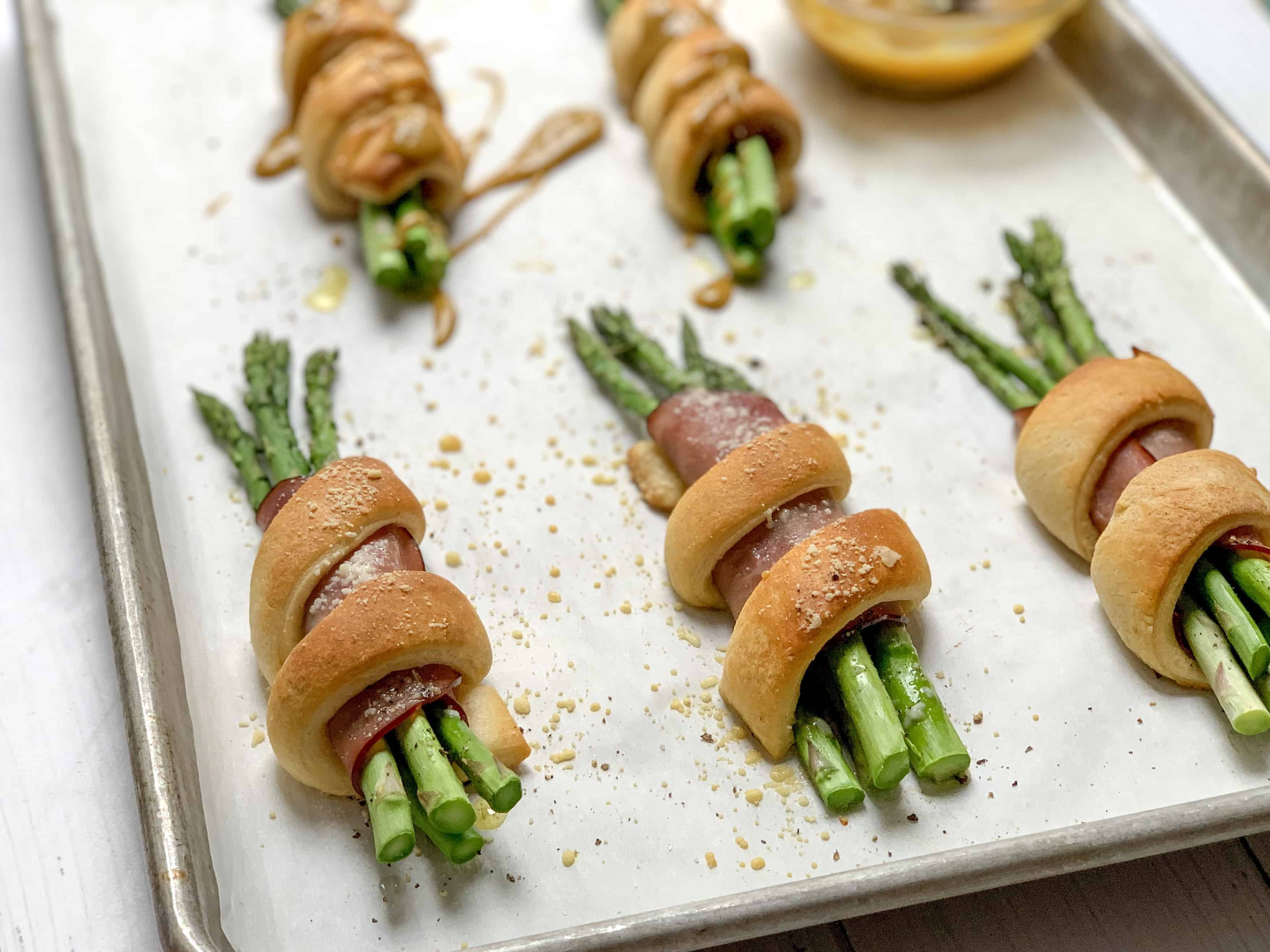 side shot of freshly baked wrapped asparagus and ham bundles with fresh parmesan on top.