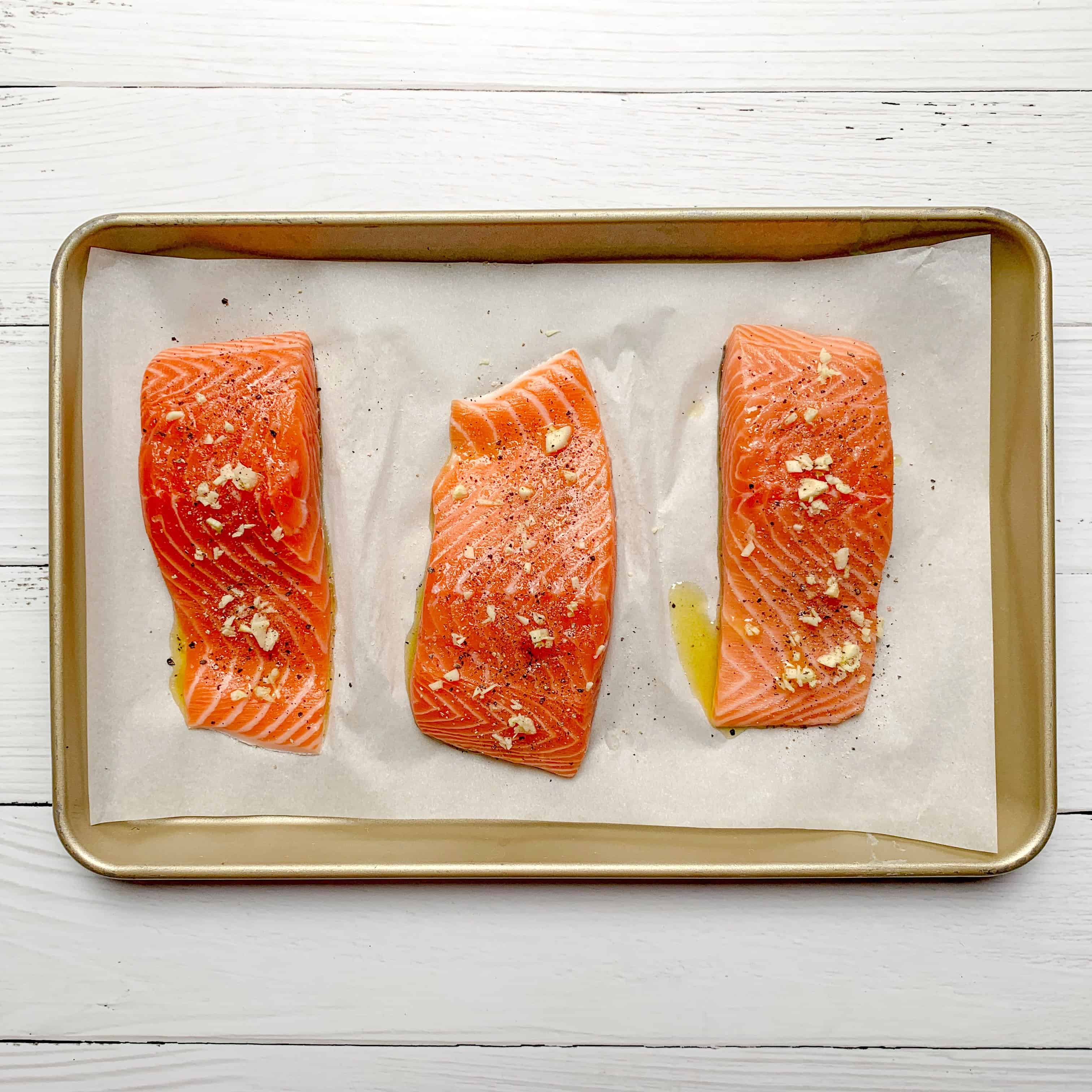3 big hunks of salmon fillets ready to be cooked on baking sheet