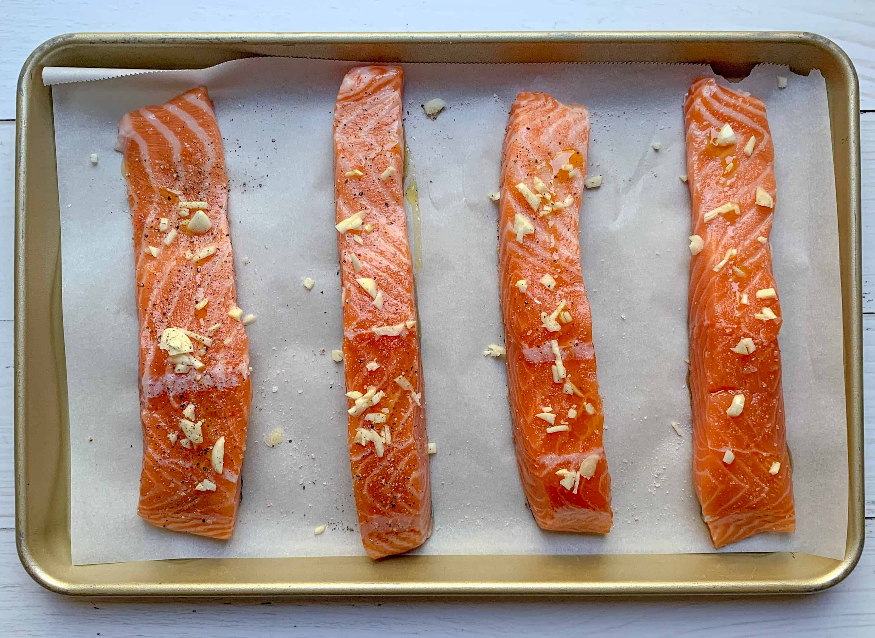 4 uncooked fillets of salmon on parchment paper lined baking sheet