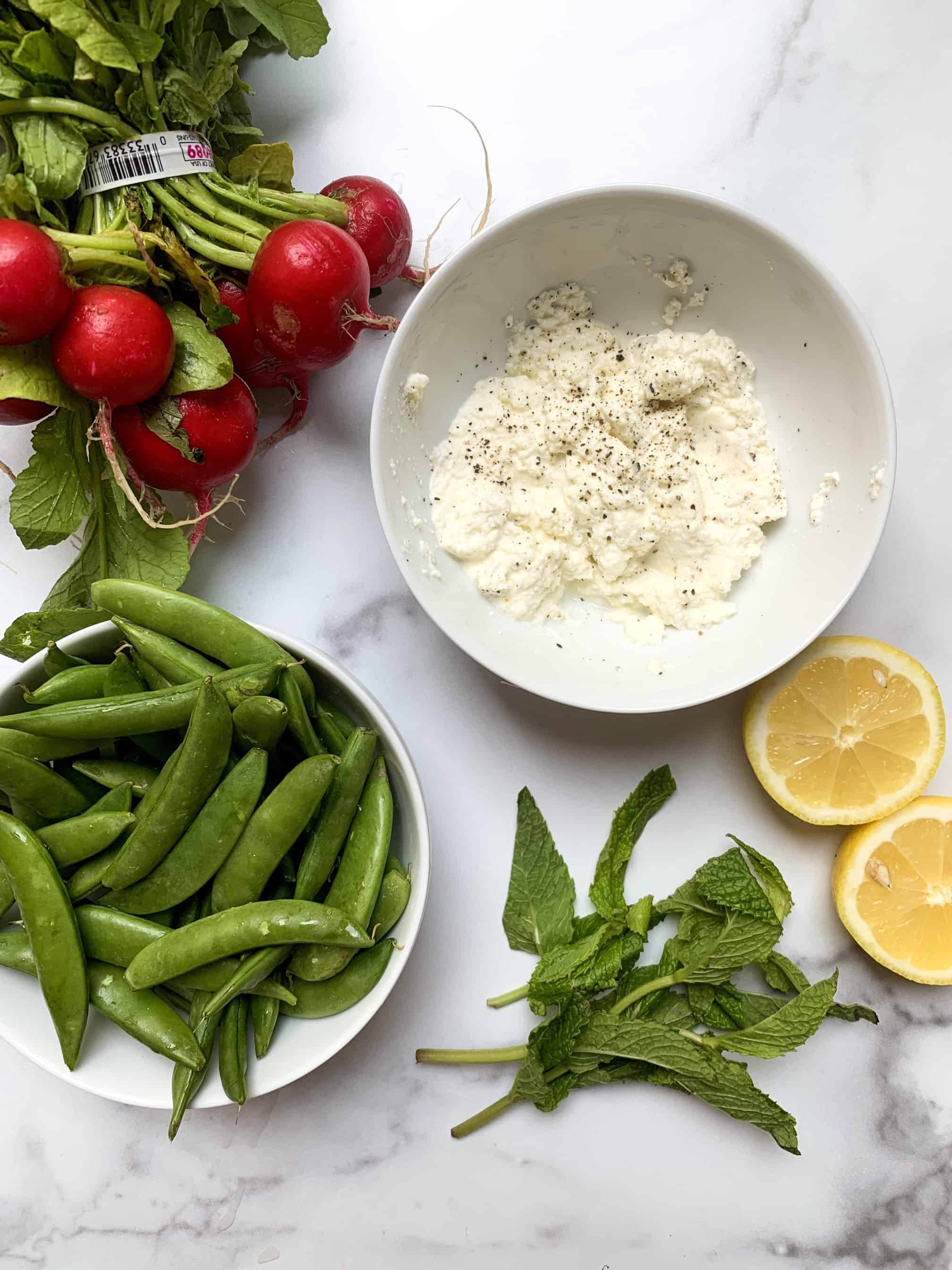 aerial shot of all ingredients needed for salad: ricotta, mint, lemon, sugar snap peas, and radishes.
