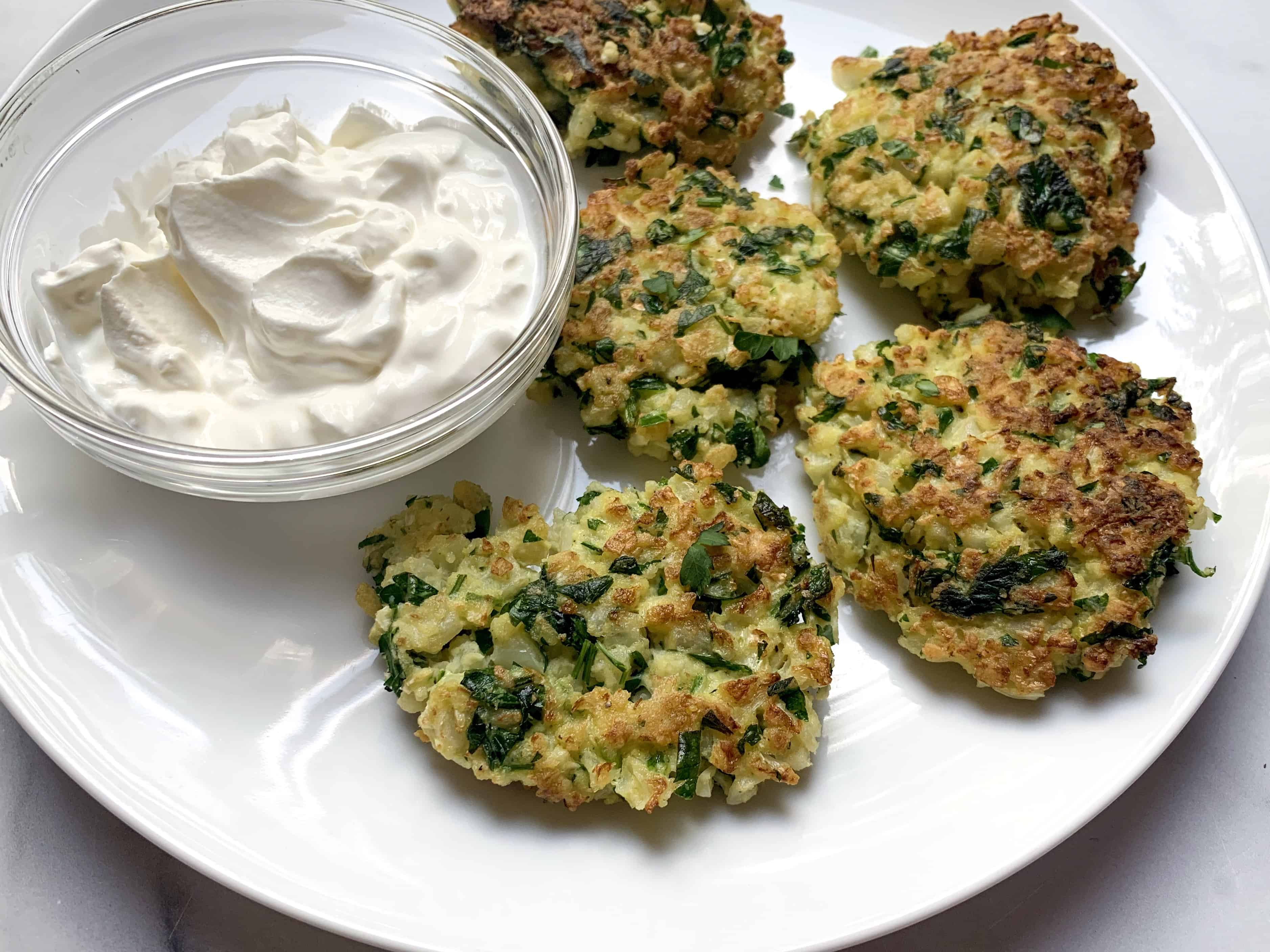 golden brown cauliflower fritters on plate with sour cream