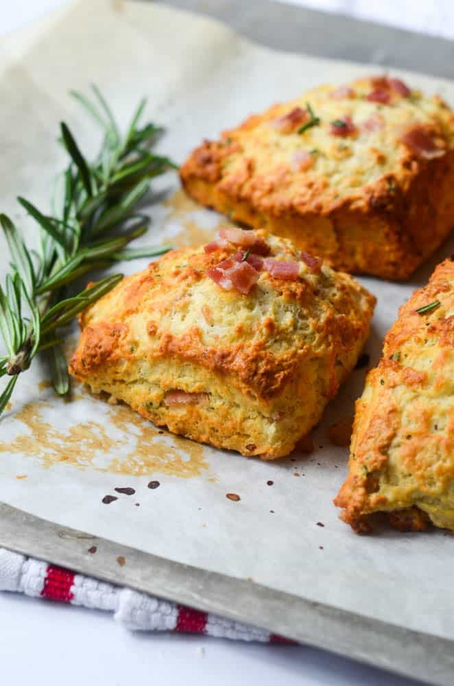 side angle shot of rosemary and bacon biscuits on baking sheet with sprig of rosemary