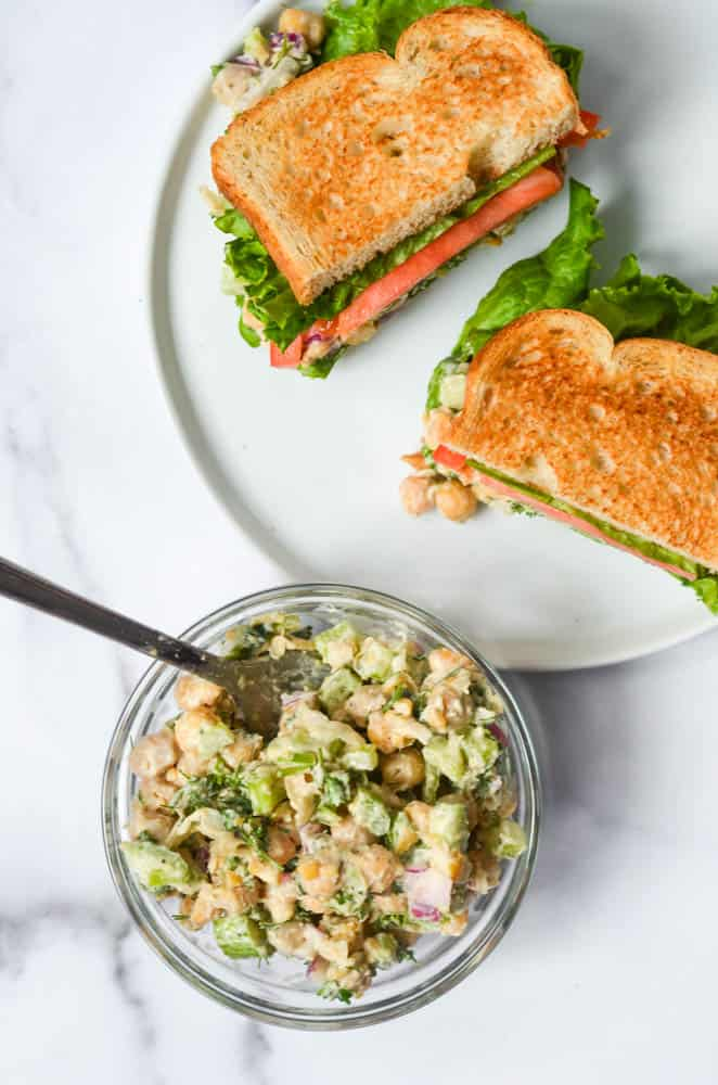 """bowl of chickpea """"chicken"""" salad with two halves of sandwiches on a white plate"""