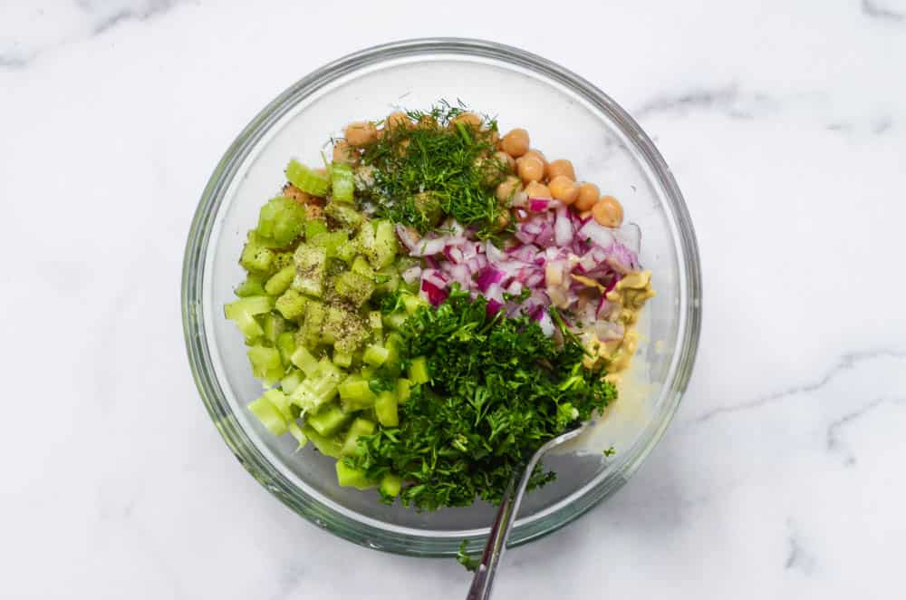 """aerial view of bowl with all of the ingredients to make chickpea """"chicken"""" salad"""