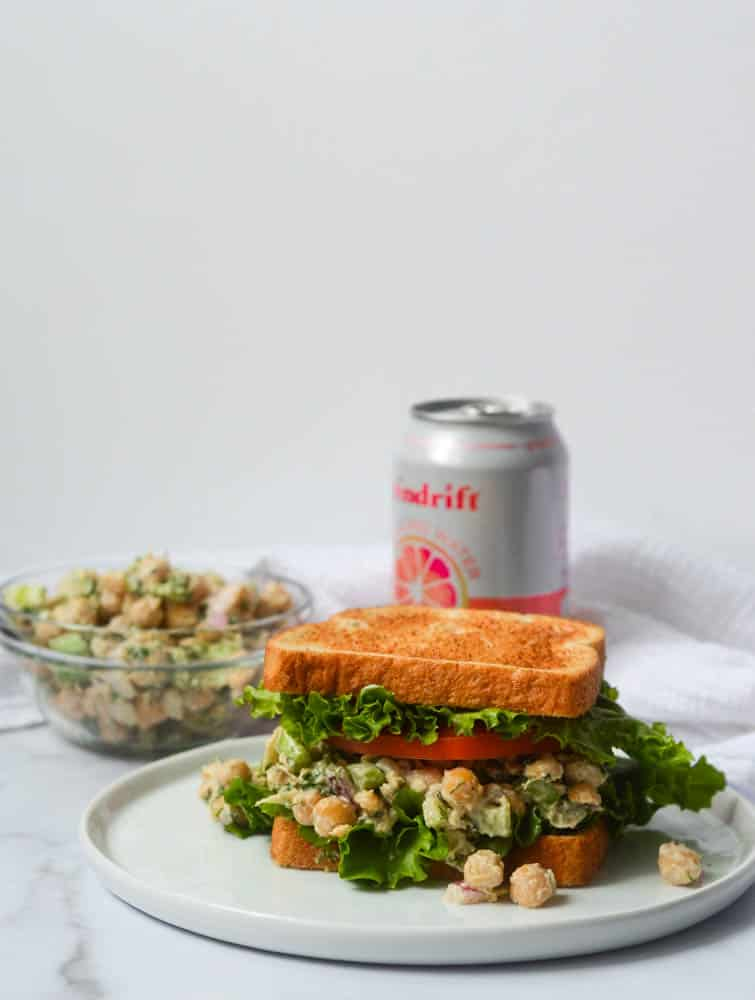 """chickpea """"chicken"""" salad on white plate with can of soda and bowl of mixture in background"""