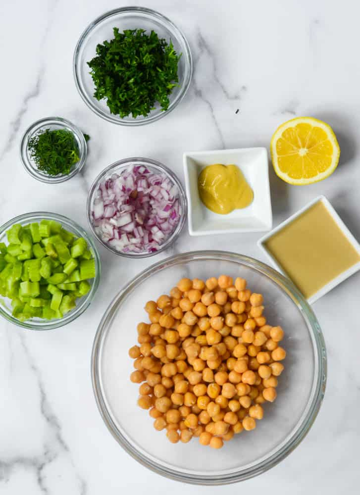 aerial view of all ingredients: bowl of chickpeas, celery, red onion, dill, parsley, dijon, tahini, and lemon.