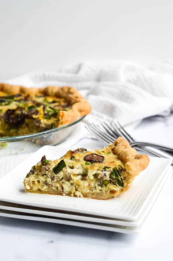side view of slice of quiche with whole quiche in the background