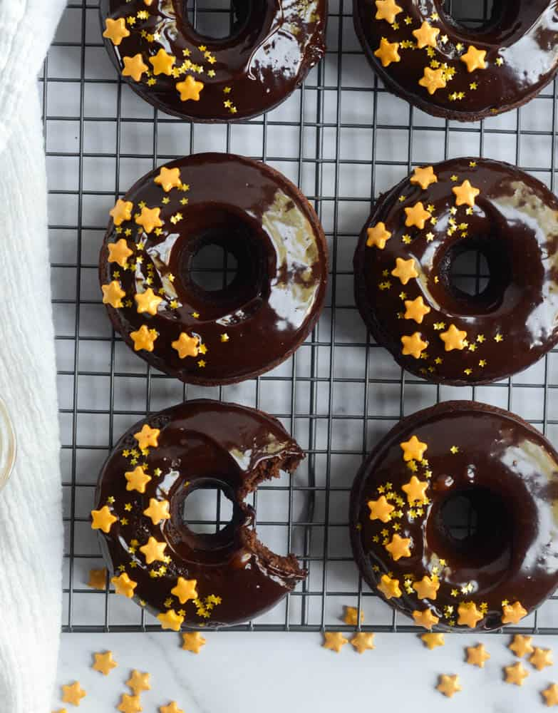 row of chocolate donuts on cooling rack with white kitchen towel