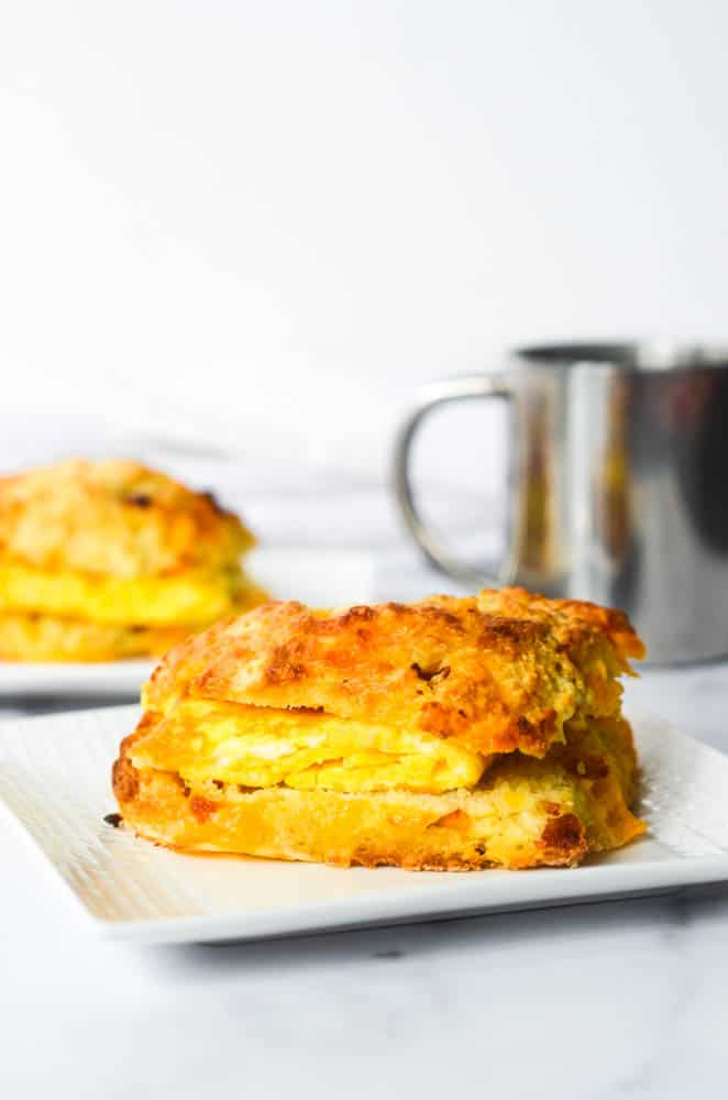close up picture of bodega style egg in middle of bacon cheddar biscuit with coffee mug and another biscuit in the background