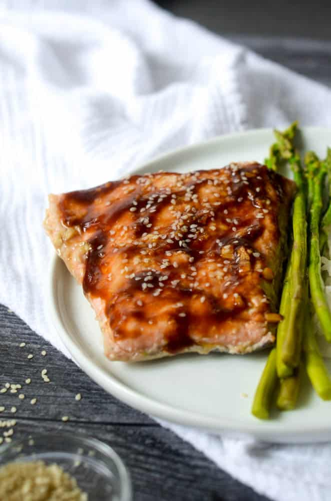 up close picture of baked teriyaki salmon with asparagus on white plate with white napkin