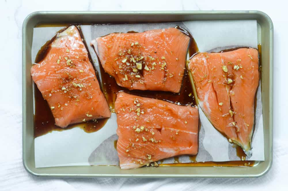 aerial view of 4 large salmon filets on baking sheet