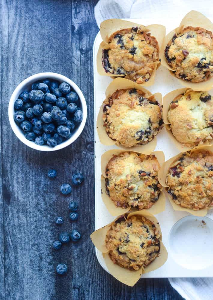 aerial view of blueberry muffins with bowl of blueberries next to it and some blueberries scattered on dark wood background