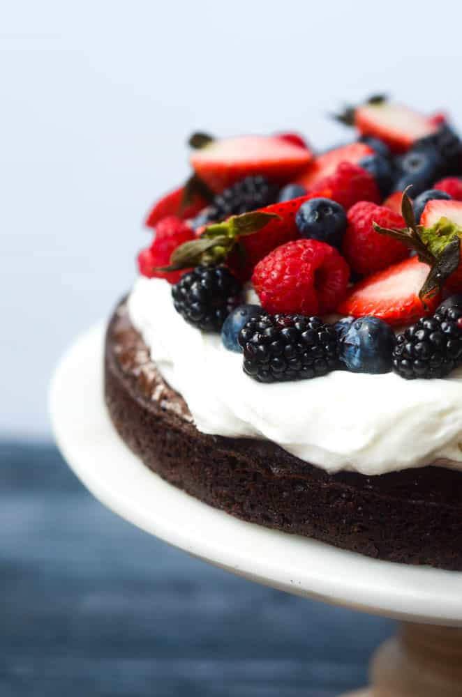 up close picture of brownie pizza with mixed berries and of whipped cream