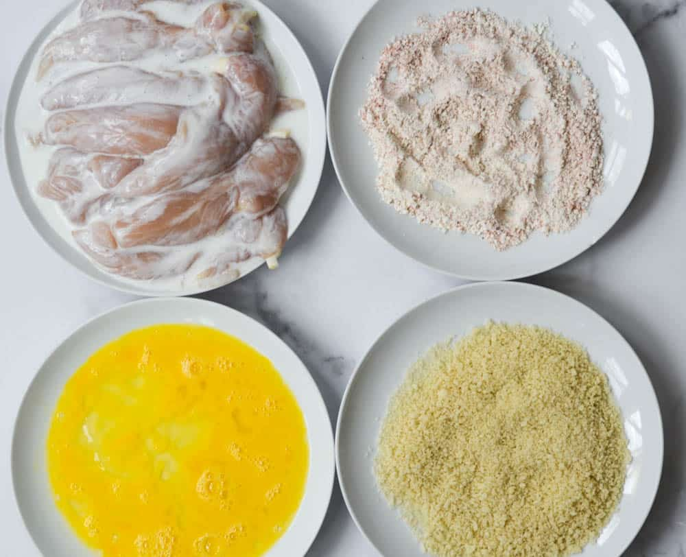 four white plates arranged in square with chicken tenders, flour mixture, eggs, and breadcrumbs.