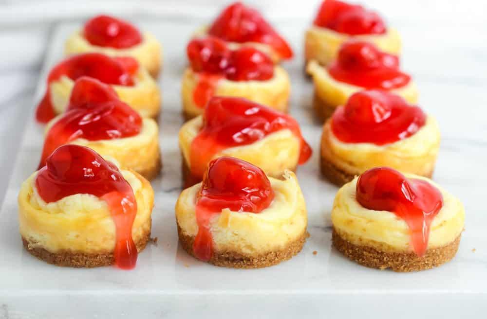 12 mini cheesecakes on white marble tray