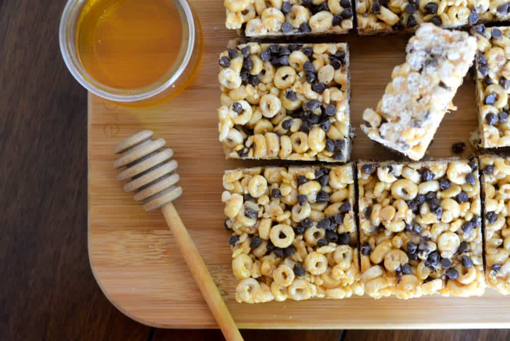 horizontal picture of homemade cereal bars on wooden cutting board with jar of honey and one bar turned on its side.