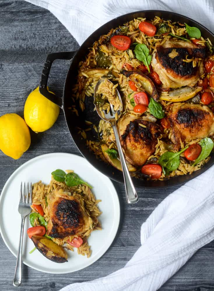 aerial view of skillet with lemon orzo chicken in it and plate where portion has been served. lemons in background.