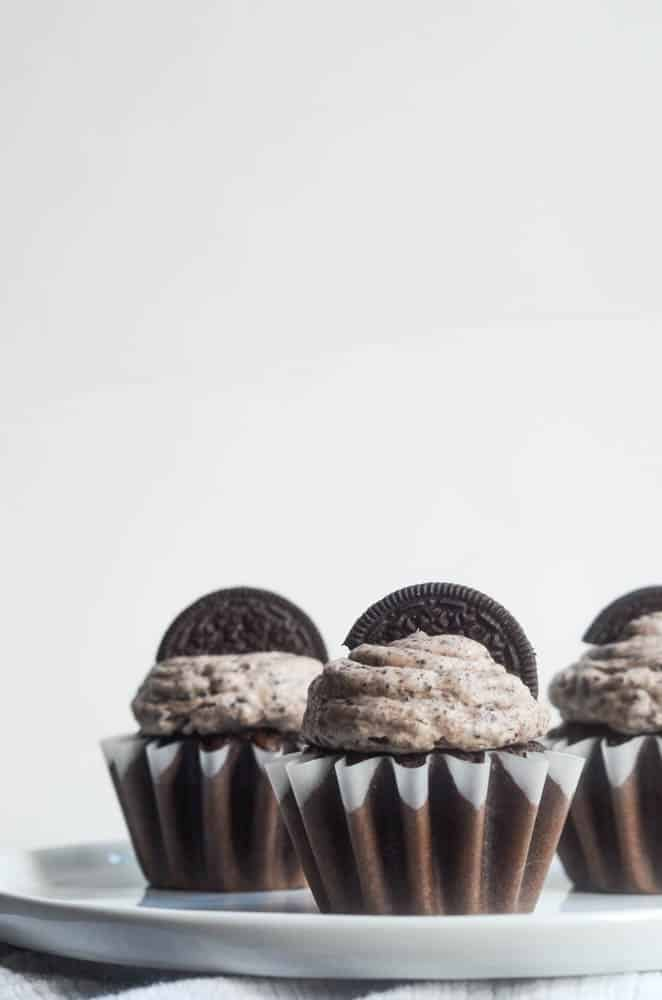 up close picture of 3 chocolate cupcakes with oreo frsoting and oreo on top