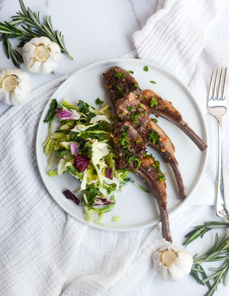 aerial view of full plate with rosemary and garlic lamb chops with side salad