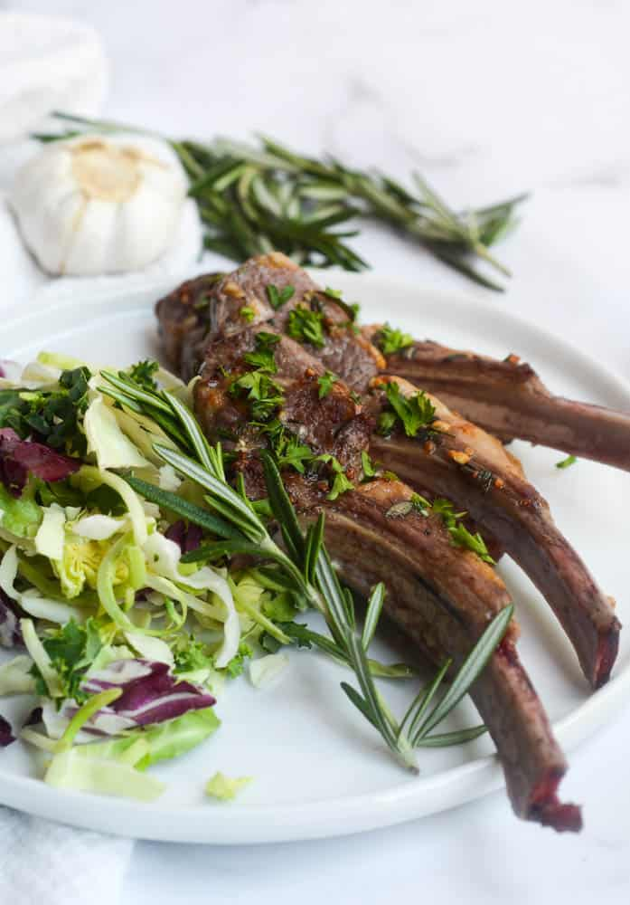 finished lamb on white plate with salad and sprig of rosemary