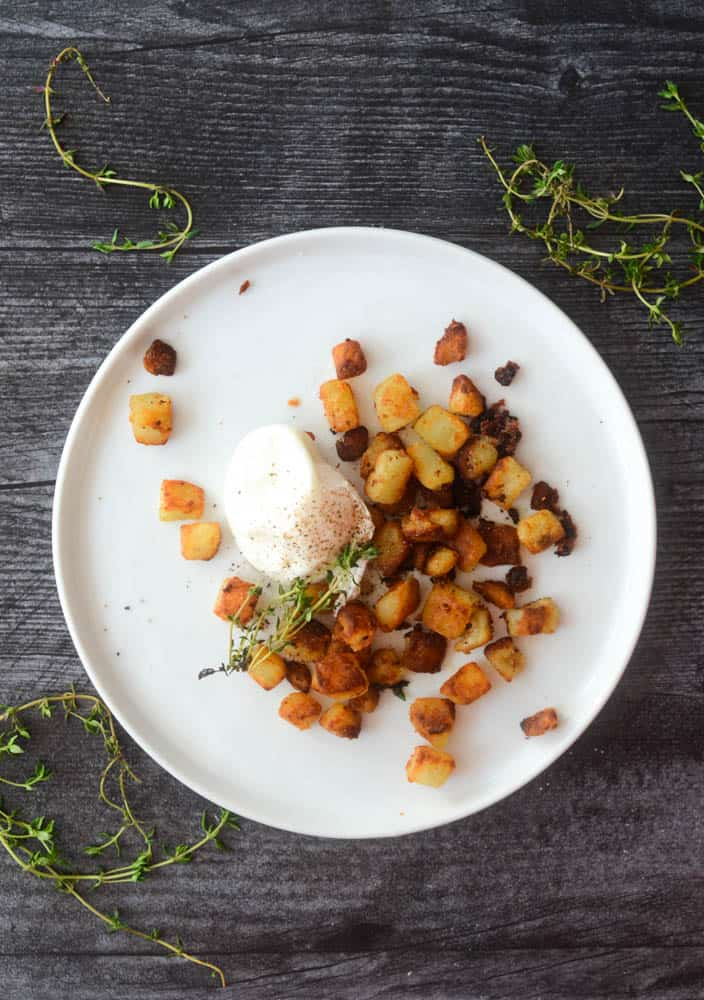 aerial shot of white plate with potatoes, poached egg, and sprig of time on black background