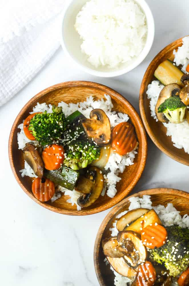 aerial view of three wooden plates with hibachi vegetables over steamed rice
