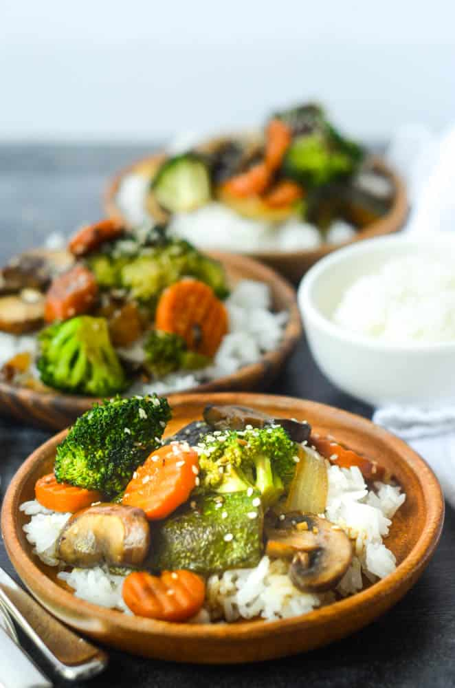 up close picture of one plate of hibachi vegetables on wooden plate with two other plates and white rice in background