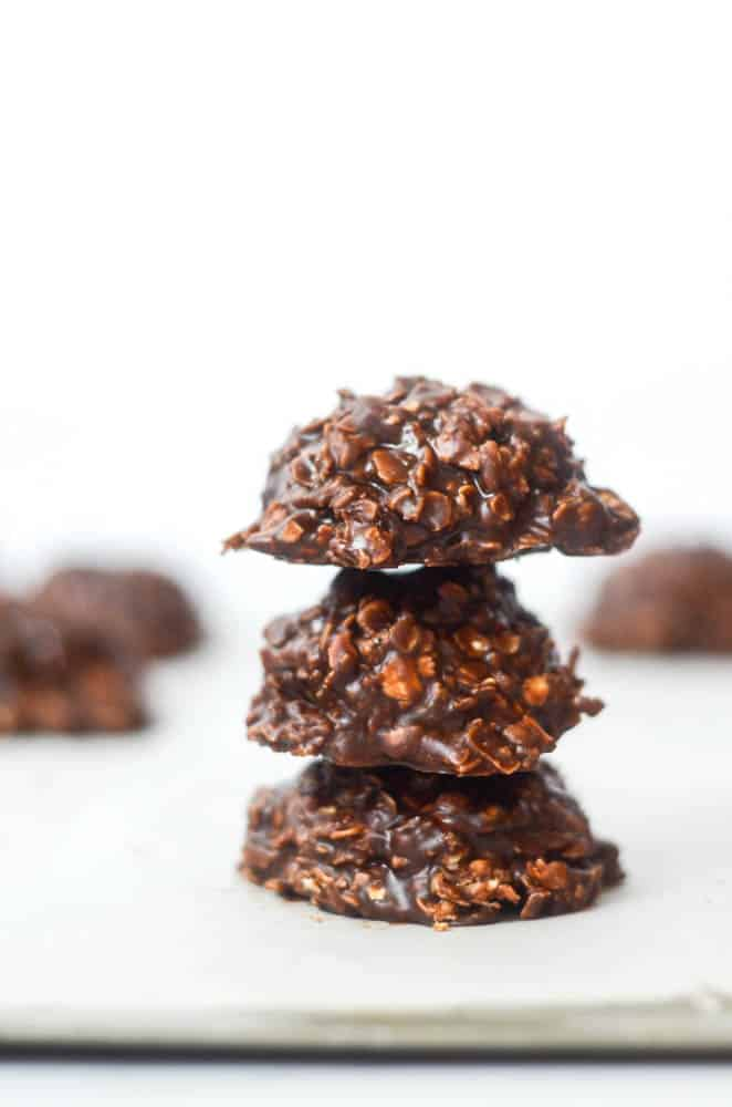 side picture of stack of three cookies with other cookies blurry in the background