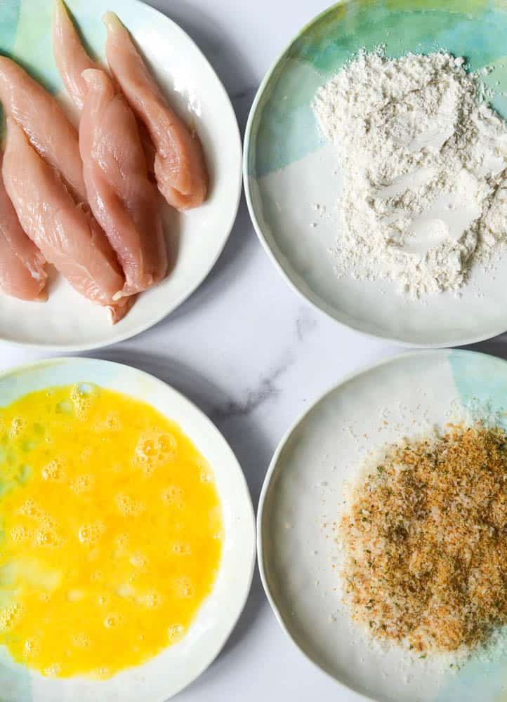 aerial view of four plates, one with chicken tenders, one with flour, one with eggs, and one with parmesan and breadcrumbs