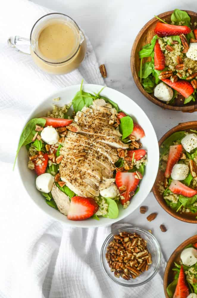 aerial shot of bowl of strawberry caprese salad with grilled chicken breast on top