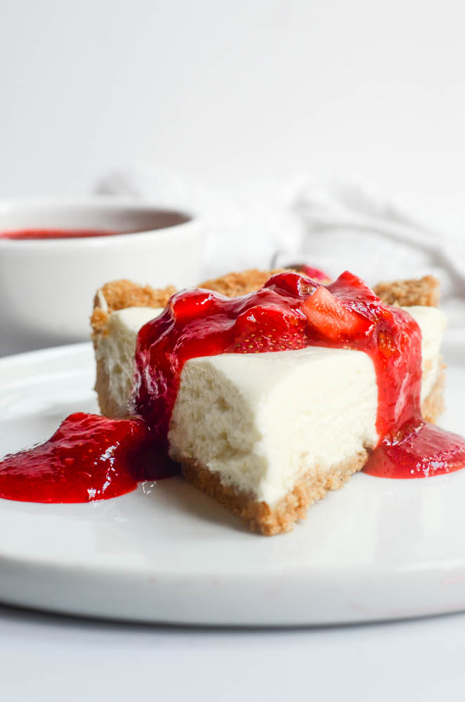 side view of strawberry cheesecake on white plate