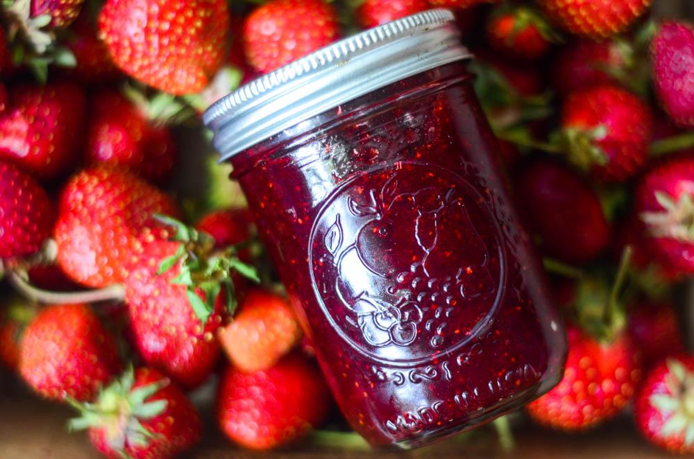 small batch strawberry jam with fresh strawberries all around