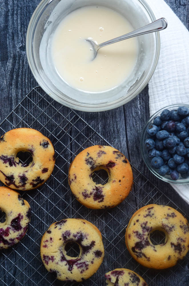 aerial picture of baked blueberry donuts before being dipped in glaze with bowl of blueberries and white cloth draped under bowl