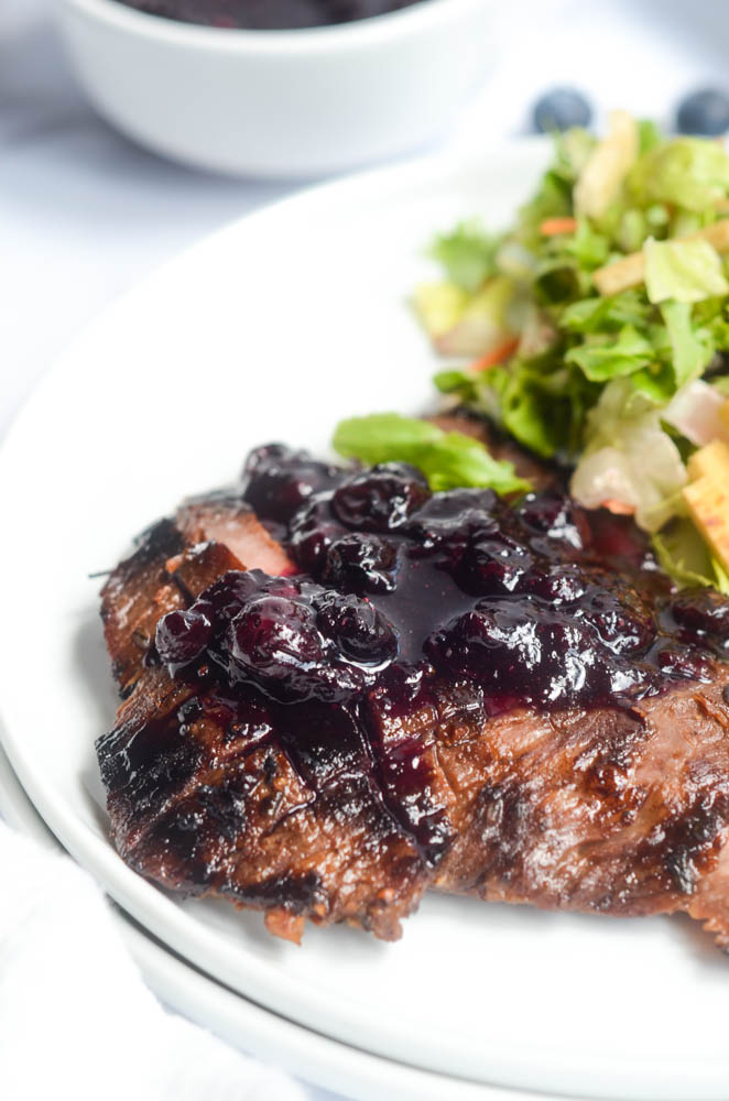 side view of flank steak with blueberry sauce on white plate with salad in background