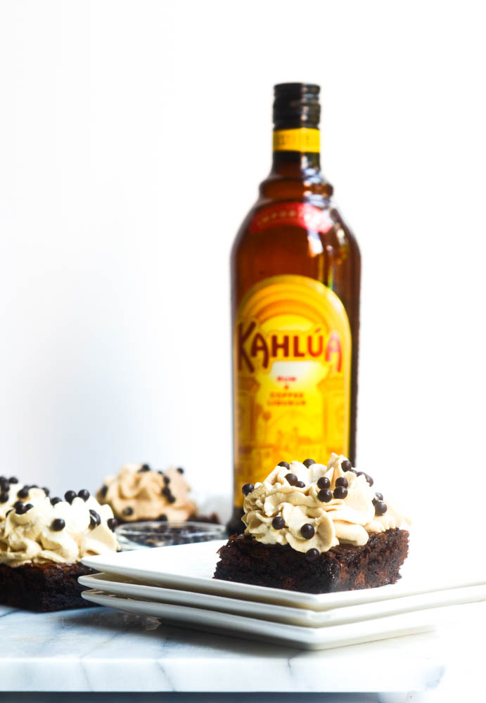 brownie with frosting on stack of white plates with kahlua bottle in background
