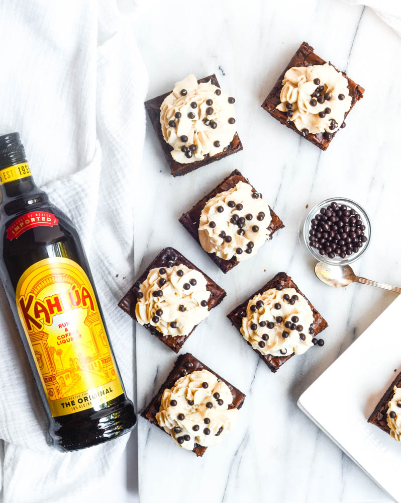 aerial shot of frosted brownies with chocolate bits in bowl and bottle of kahlua
