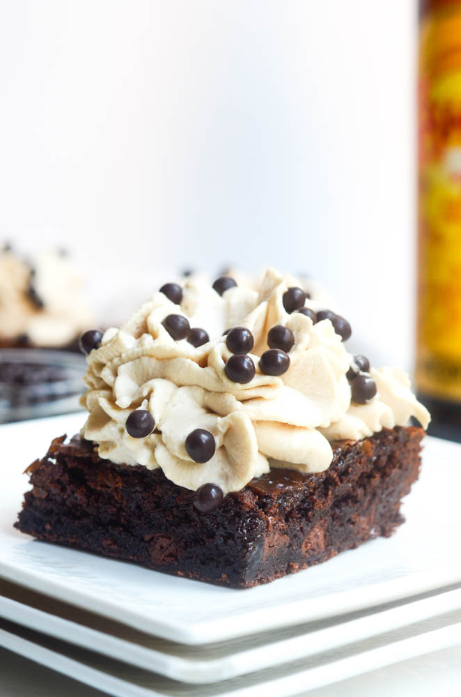 close up of brownie with frosting on white plate and chocolate nibs