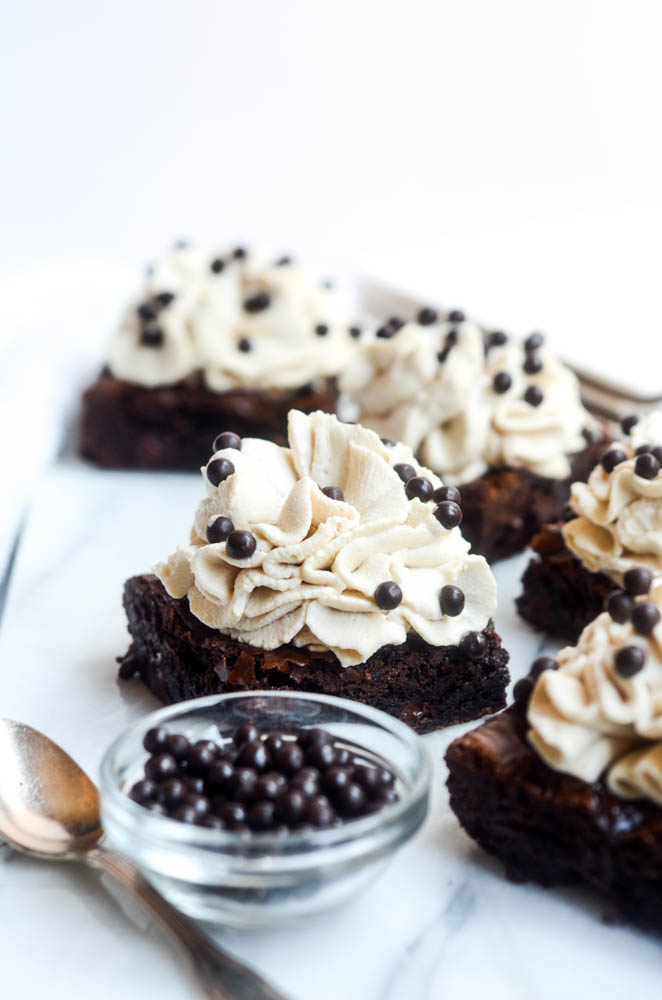 close up of one brownie with kahlua frosting and spoon and bowl of chocolate nibs