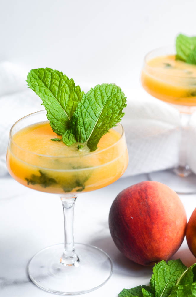 close up of peach mojito with two large mint leaves sticking out.  peaches, limes and mint are scattered around bottom of wine glass.