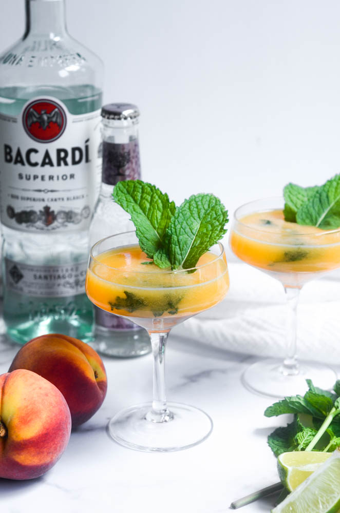 two peach mojitos around peaches, mint, and limes with bottle of bacardi and soda water in the background