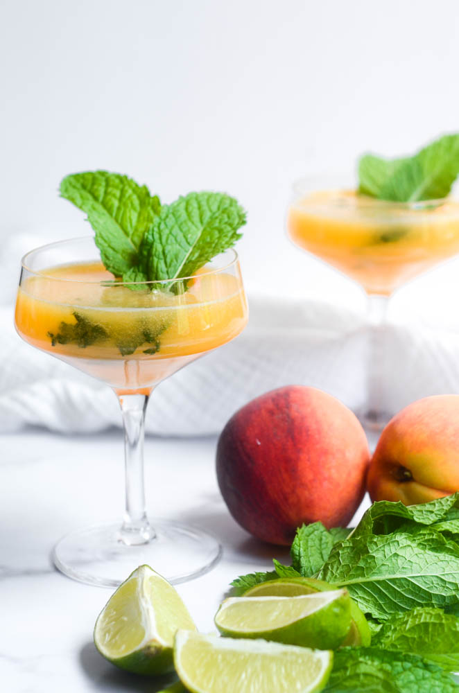 close up of peach mojito in wide mouth wine glass with mint, peaches, and limes in the background