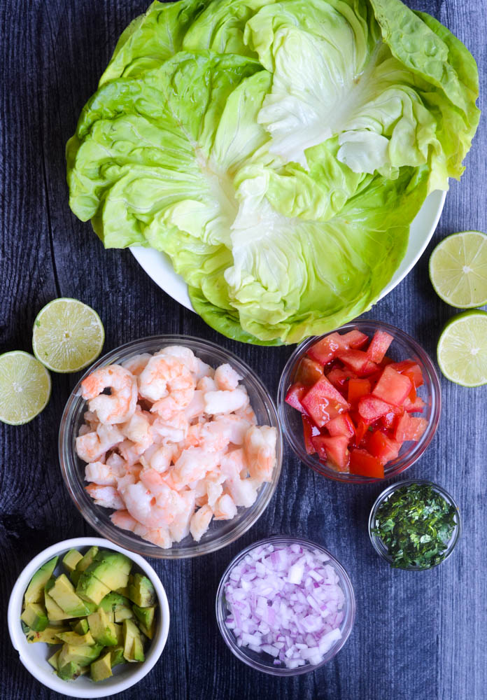 flat lay with every ingredient in a separate glass or white bowl: avocado, red onion, cilantro, cooked shrimp, tomato, halved limes, and butter lettuce