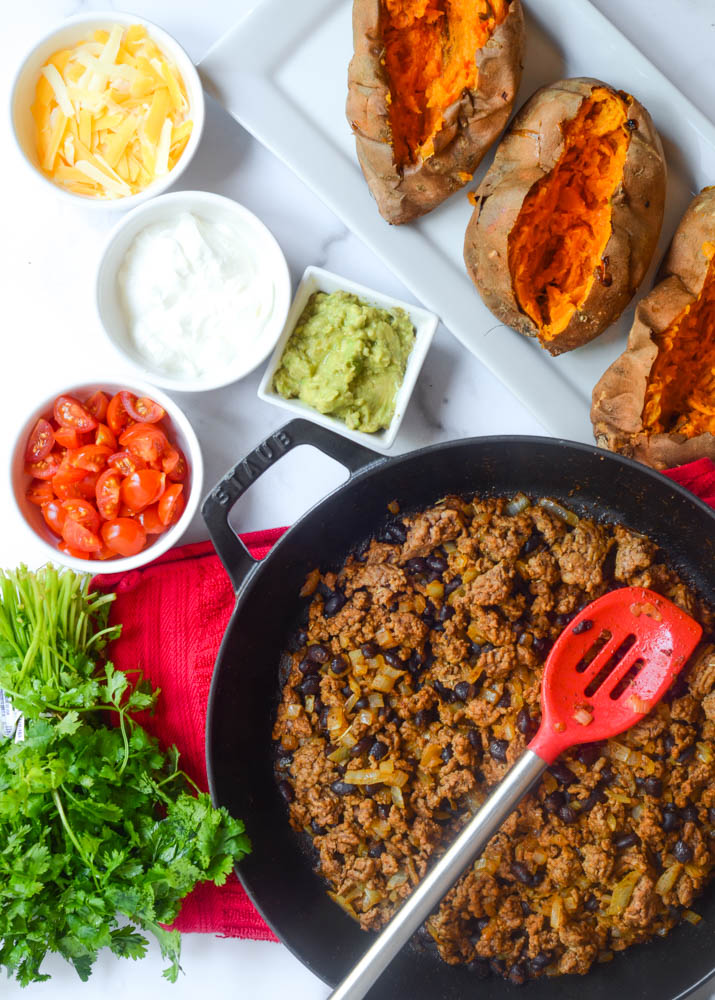 flat-lay of ingredients needed: sweet potatoes, skillet with taco meat in it, and separate bowls of toppings