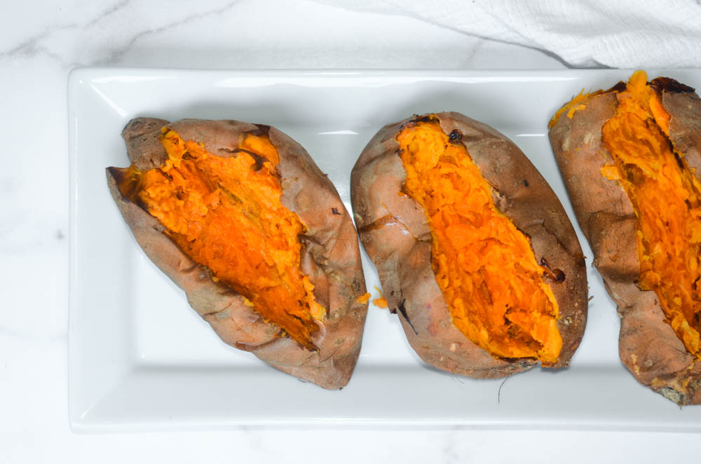 aerial photo of 3 baked sweet potatoes opened up on white tray