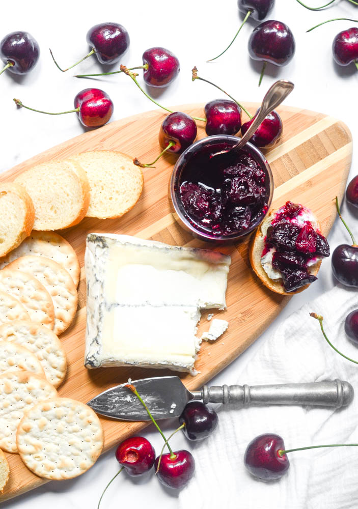 aerial view of wooden cutting board with cheese, crackers, bread, and cherry spread.