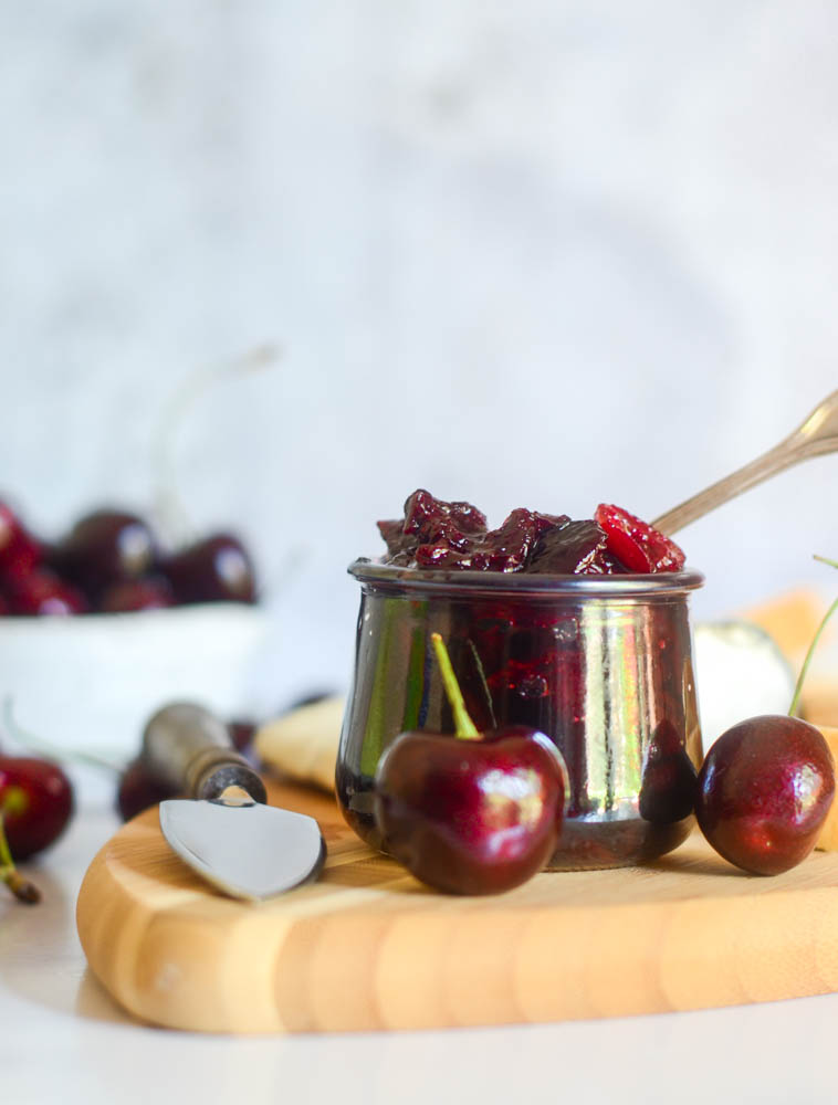 front view of glass jar of compote with cherry on wooden cutting board and cherries and cheese in the background.