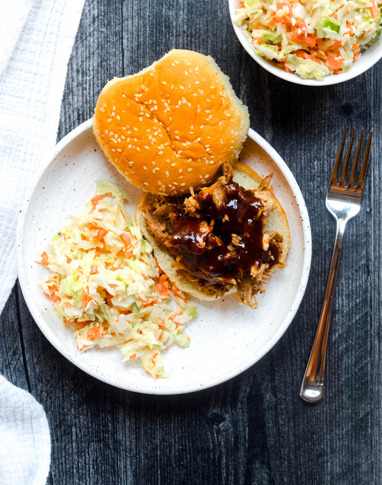 white plate with BBQ pork sandwich and coleslaw against black background